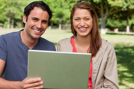 Two friends happily looking ahead as they hold a tablet in a sunny grassland photo