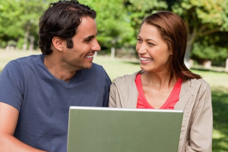 Two friends joyfully smiling as they look at each other while holding a tablet in a park on a sunny day photo