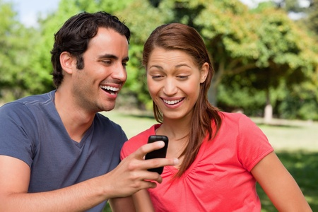 Man laughing as he shows something on his phone to his friend who is laughing happily while sitting in a bright grassland photo
