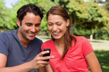 Two friends smiling as they are looking at something on a mobile phone while sitting in a bright grassland area photo