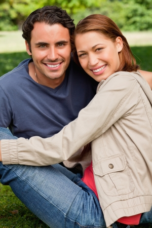 Two friends smiling and looking in front of them as they sit next to each other on the grass in a bright parkland photo