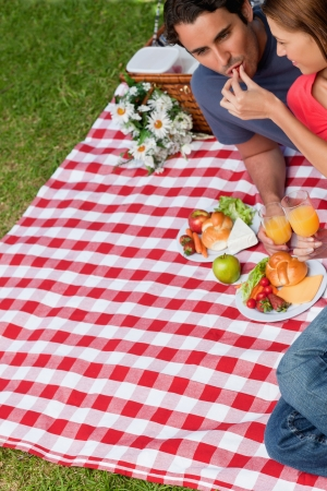 Young woman feeding her friend as they lie next to each other on a blanket with a picnic basket and food photo