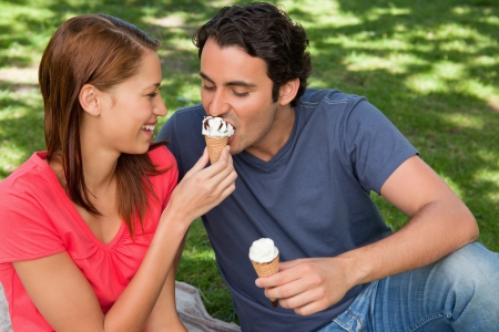 woman with ice cream: Smiling woman feeding her friend an ice cream cone as they sit next to each other on the grass Stock Photo