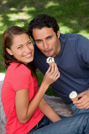 Two smiling friends looking towards the sky while holding ice cream and sitting on grass photo
