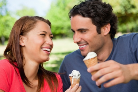 Two friends laughing while looking at each other and holding ice cream in a sunny park photo