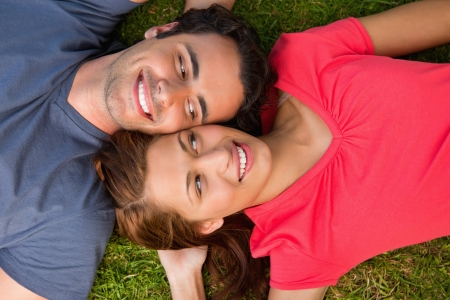 Two friends smiling while looking at each other as they lie head to shoulder with an arm behind their head on the grass Stock Photo - 13667094