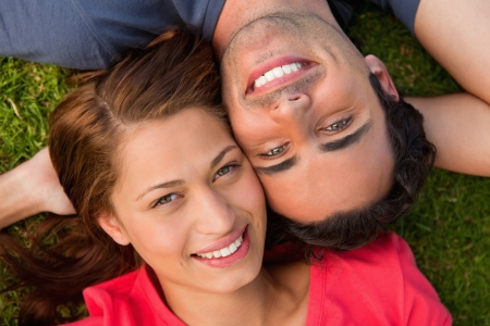 Close-up of two friends smiling while looking towards they sky as they lie head to shoulder with an arm behind their head on the grass photo