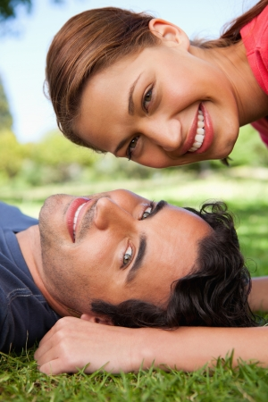 Smiling woman looking towards the side while her head is above her smiling friend's head as he is lying on the grass photo