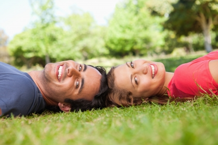 Two friends smiling while looking towards the side as they lie head to head on the grass photo