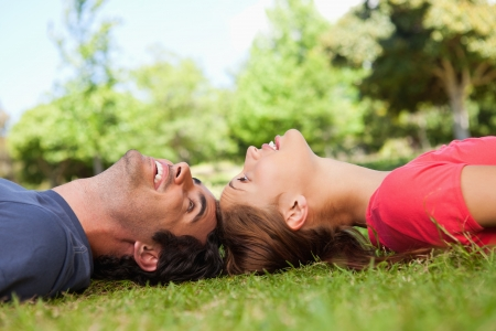 Two friends smiling while looking at each other as they lie head to head on the grass photo