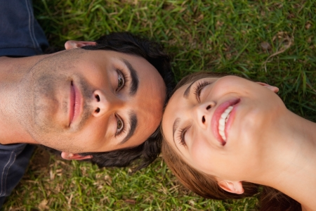 Close-up of two friends smiling while looking at each other as they lie head to head on the grass photo
