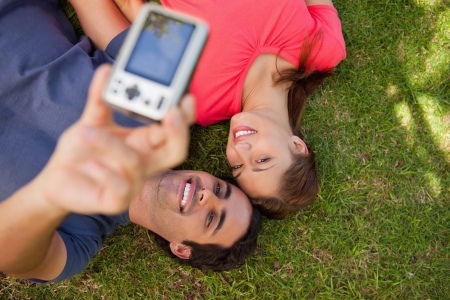 Two smiling friends using a camera while lying side by side on the grass photo