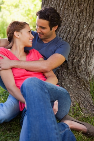 Man looking at his smiling friend as he holds her while they sit together against the trunk of a tree photo