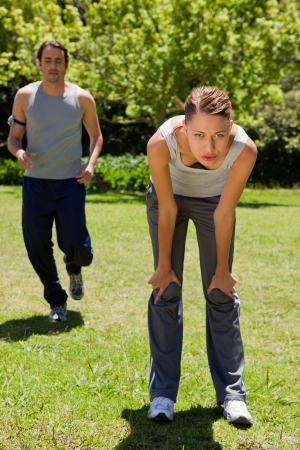 recover: Woman bending over to recover while a man is jogging close to her in the background Stock Photo