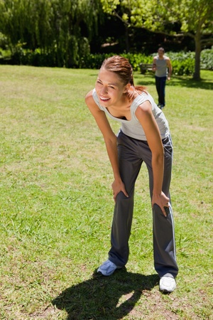 Woman smiling as she bends over recovering while a man is walking towards her in the background Stock Photo - 13667423
