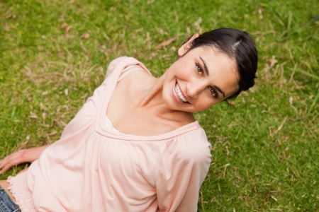 head tilted: Woman smiling with her head tilted to one side as she lies down on the grass