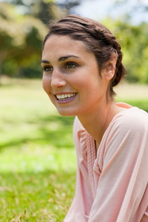 Young woman smiling while looking straight ahead of her while sitting on the grass photo
