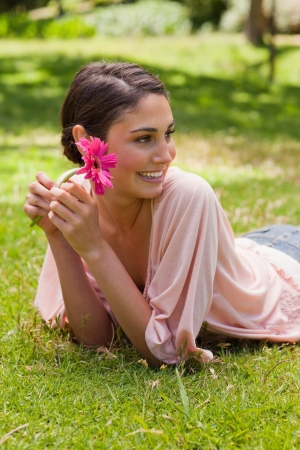 Smiling woman lying down in grass while looking towards the side and holding a flower in her hand photo