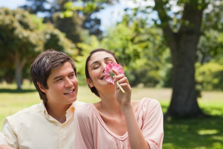they are watching: Smiling man watching his friend while she is smelling a pink flower as they are both sitting down on the grass