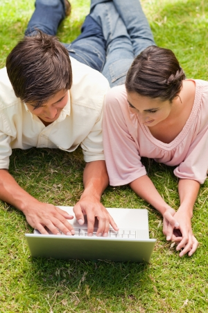 Two friends smiling while watching something on a laptop as they lie down together in the grass  Stock Photo - 13667210