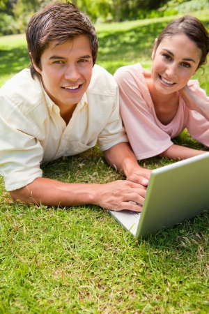 Two friends with happy expressions looking towards the side while using a laptop as they they lie together on the grass photo