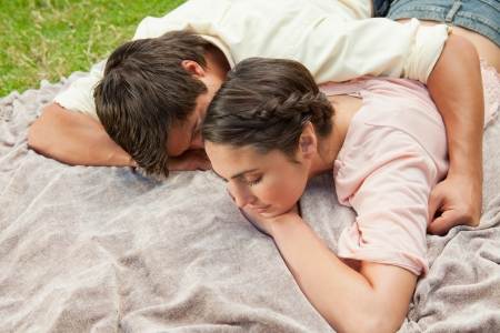 Man with his arm around his female friend while they are lying prone on a grey blanket int the grass photo