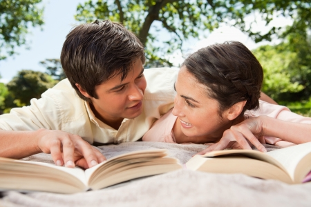 Man and a woman looking at each other while reading books as they lie prone on a grey blanket in the grass photo