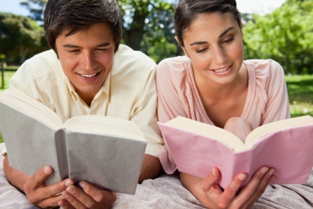 Woman and a man smiling as they are reading while lying prone on a grey blanket in the grass Stock Photo - 13668436
