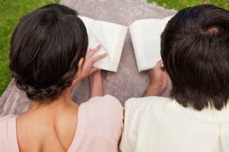 Rear view of a man and a woman reading books while lying prone on a blanket in the grass photo