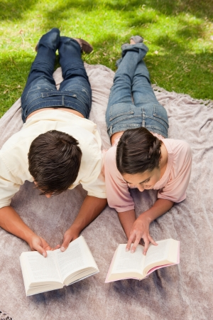 Elevated view of a man and a woman reading books while on a lying next to each other on a blanket in the grass photo