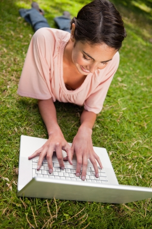 Smiling woman using a white laptop as she is lying prone in grass photo