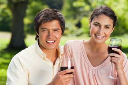 Woman and a man looking straight ahead while holding glasses of red wine in a park Stock Photo - 13668354