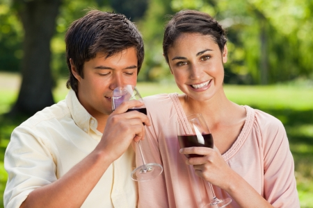 Woman looking ahead and smiling while her friend drinks from a glass of red wine in a park Stock Photo - 13667613
