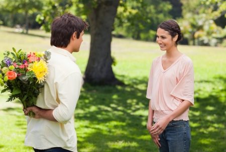 Woman smiling as she greets her friend who is holding flowers behind his back Stock Photo - 13670980