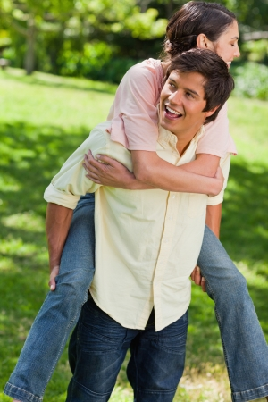 Man smiling and looking towards the side while he is carrying his friend on his back in a park photo