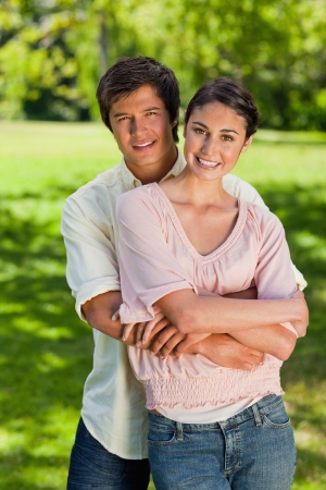 smiling man: Man and woman smiling as he has his arms around her abdomen in a park