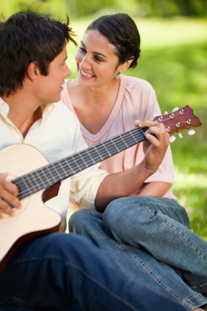 Man playing a guitar and looking at his smiling friend while sitting on grass with her photo