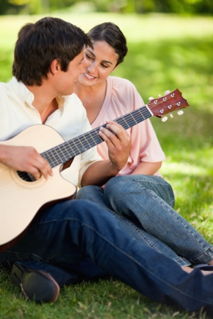 Woman smiling while looking at her friend play the guitar as they sit on grass togethe photo