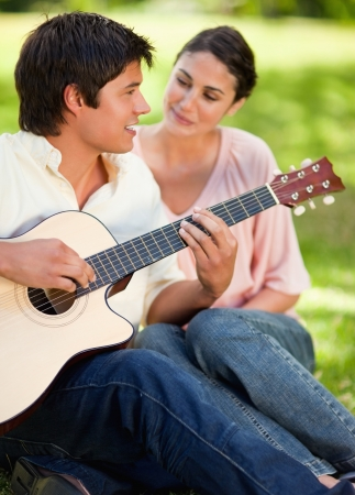Man looking ahead and smiling as he is playing the guitar and being watched by his friend who is sitting next to him on the grass photo