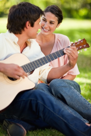 Woman smilng while looking at her friend who is playing the guitar as they both sit on the grass photo
