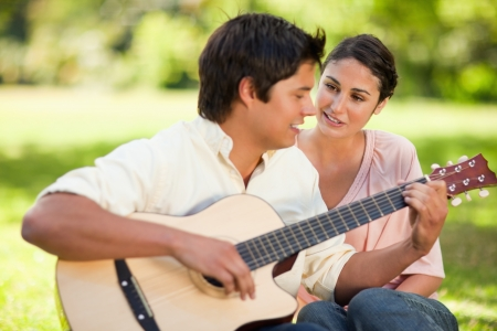 Man playing a song on the guitar while his smiling friend watches him as they are both sitting on the grass Stock Photo - 13671470