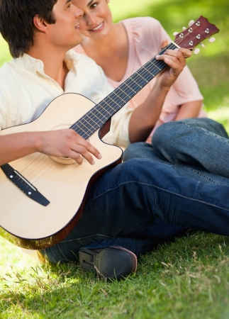 Man playing a song on the guitar while his smiling friend watches and listens to him as they sit on the grass Stock Photo - 13671220