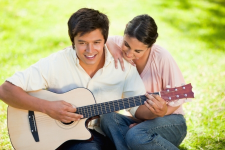 Woman putting her hand on her smiling friends shoulder while he plays the guitar as they both sit on the grass photo