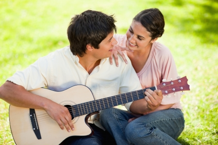 Man plays the guitar while looking at his friend who has her hand on his shoulder as they both sit on the grass photo