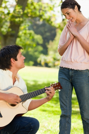 Woman standing and smiling with her hands joined as she admires her friend who is playing the guitar photo