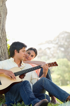 Man looking downwards while playing the guitar as his friend watches him photo