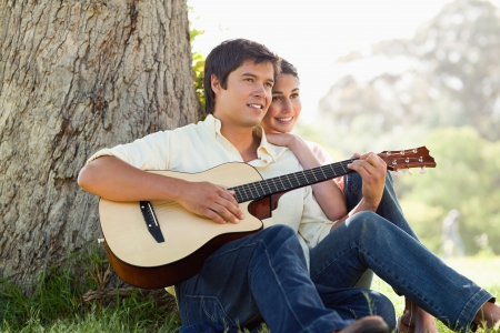 Man and his friend look into the distance as they listen to him playing the guitar while sitting against the trunk of a tree photo