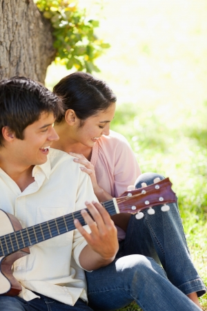 Woman laughing while leaning against her friend who is playing the guitar as they both against the trunk of a tree photo