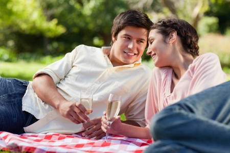 Man smiling as he looks at his friend while they touch glasses of champagne and lie down on a picnic blanket photo