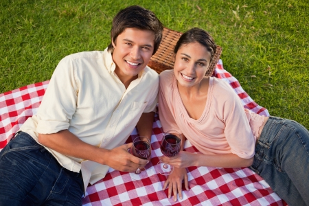 Man and a woman looking towards the sky and holding glasses of red wine while lying on a red and white picnic blanket photo